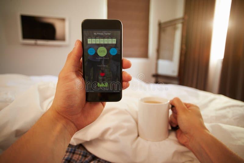 Человек в кровати смотря медицинский контроль App на мобильном телефоне стоковое изображение rf