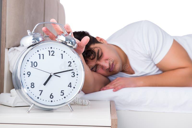 Человек в кровати страдая от инсомнии стоковое фото