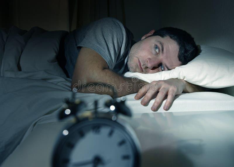 Человек в кровати с глазами раскрыл страдая инсомнию и стоковая фотография