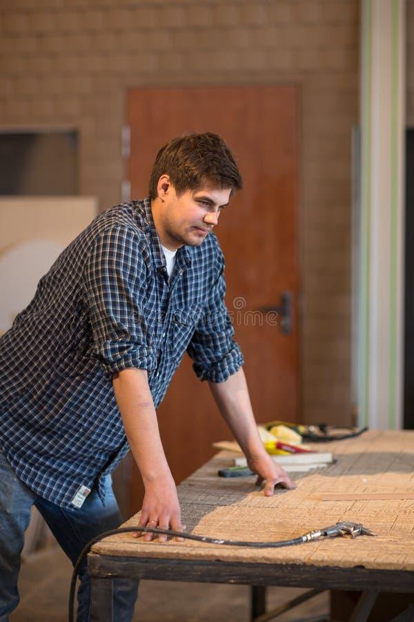 Человек в мастерской, мастерской плотничества обдумывает работу, образ жизни стоковое изображение