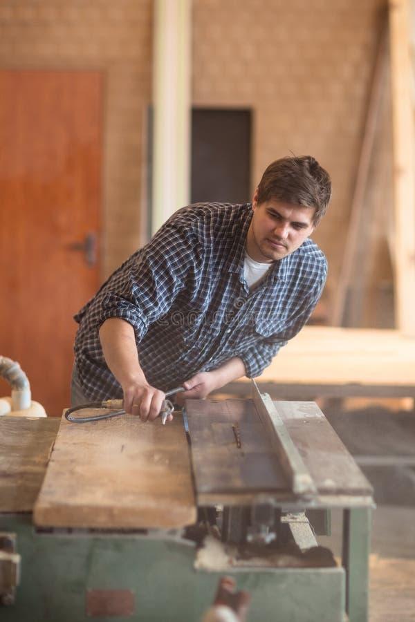 Человек в мастерской, мастерской плотничества tidying, пылиться пневматический стоковое изображение