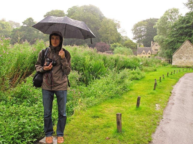 Человек в дожде с зонтиком стоковые изображения rf