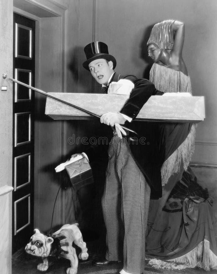 Человек в официально одежде и собаке пробуя звенеть колокол с его идя ручкой (все показанные люди нет более длинных прожития и n стоковые изображения