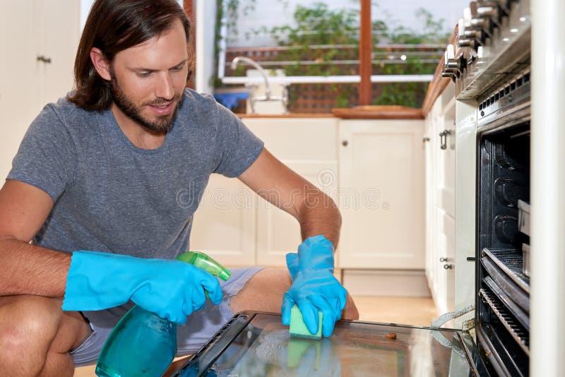 Человек в печи чистки кухни стоковая фотография rf