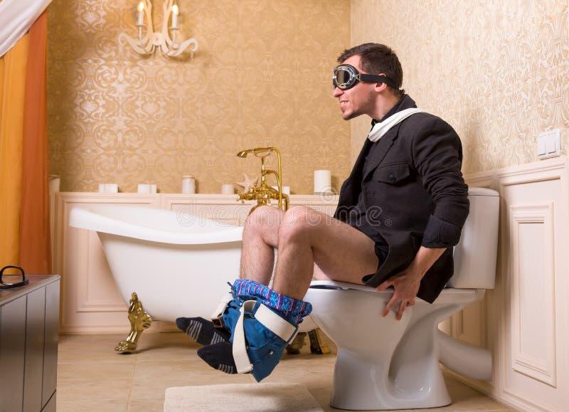 Человек в пилотных стеклах сидя на шаре туалета стоковые фото