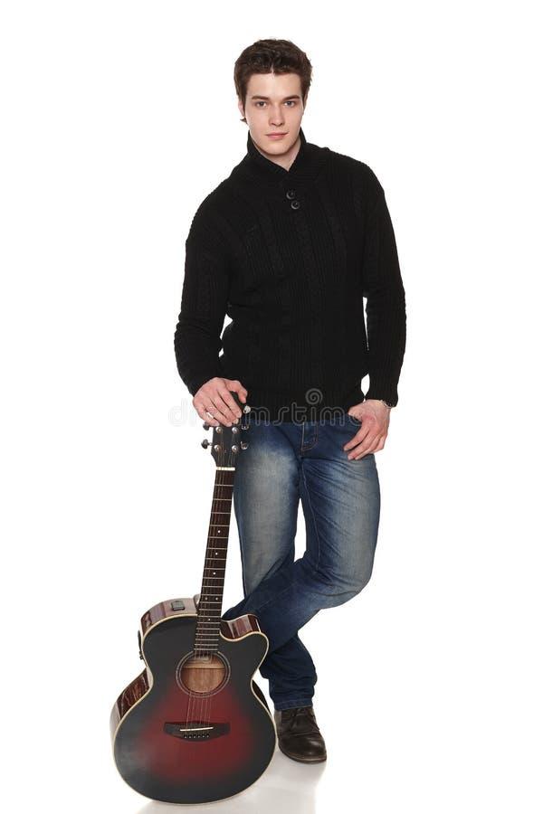 Человек в полнометражном положении с акустической гитарой стоковое изображение