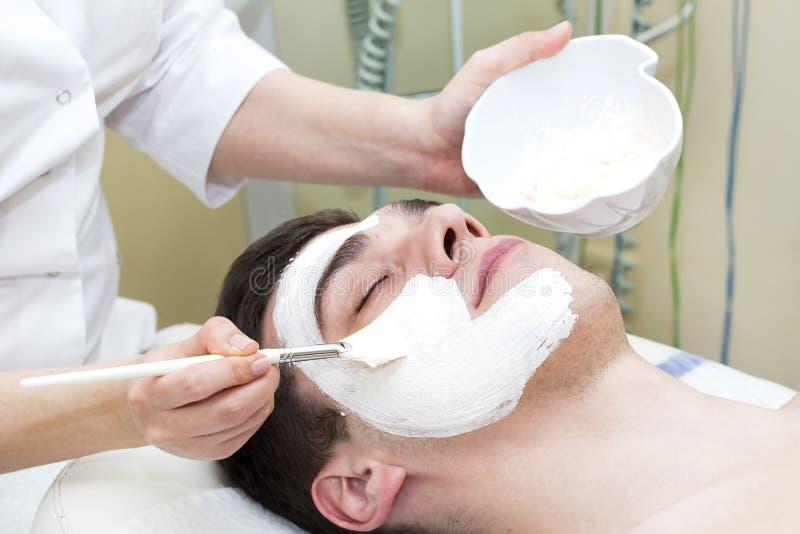Человек в процедуре по косметики маски стоковое изображение rf