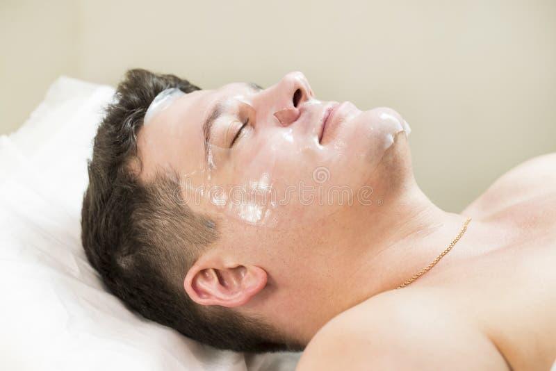 Человек в процедуре по косметики маски стоковые фото