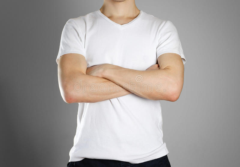 Человек в пустой белой футболке Парень сложил его руки на его ches стоковое фото