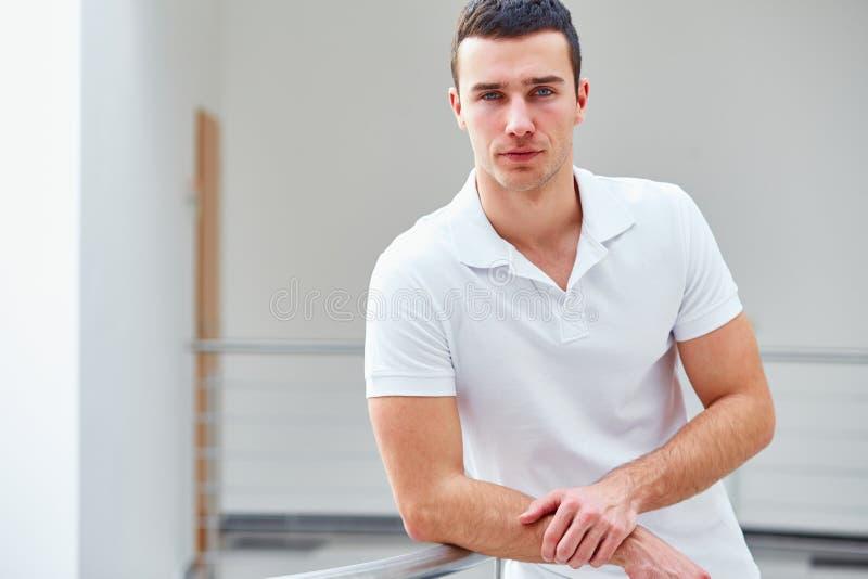 Человек в рубашке поло стоит склонность на перилах стоковые изображения rf