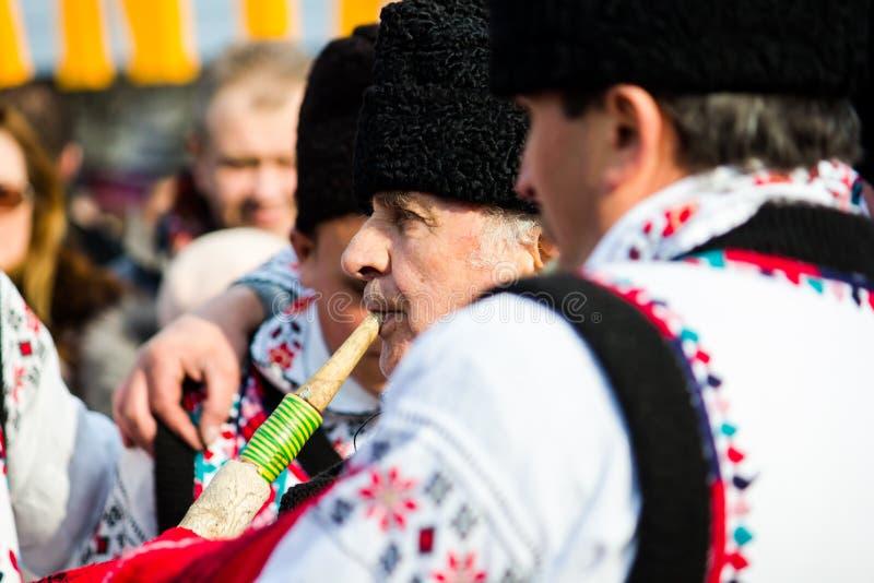 Человек в румынском традиционном костюме, играя трубу стоковое изображение rf