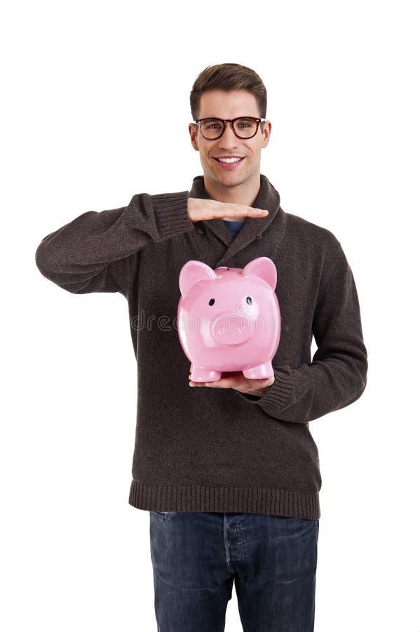 Человек в свитере защищает piggybank стоковые изображения