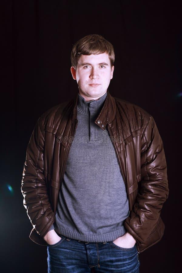Человек в свитере и куртке джинсов на черной предпосылке стоковая фотография rf