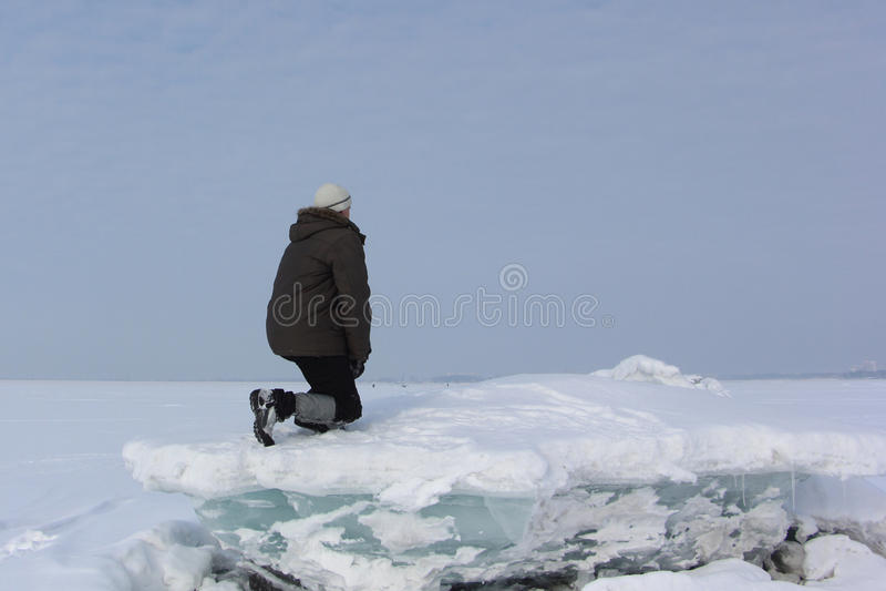 Человек в серой крышке сидя на блоке льда смотря afar стоковая фотография