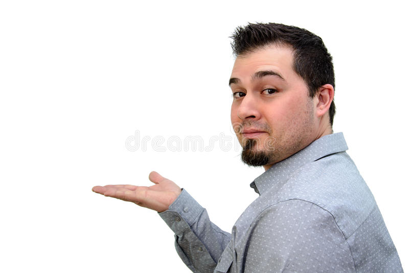Человек в серой рубашке держа вне руку для того чтобы представить что-то стоковые фото