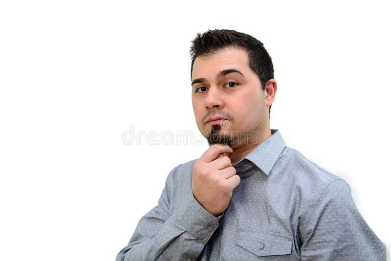 Человек в серой рубашке штрихуя Chin на белом фоне стоковые изображения