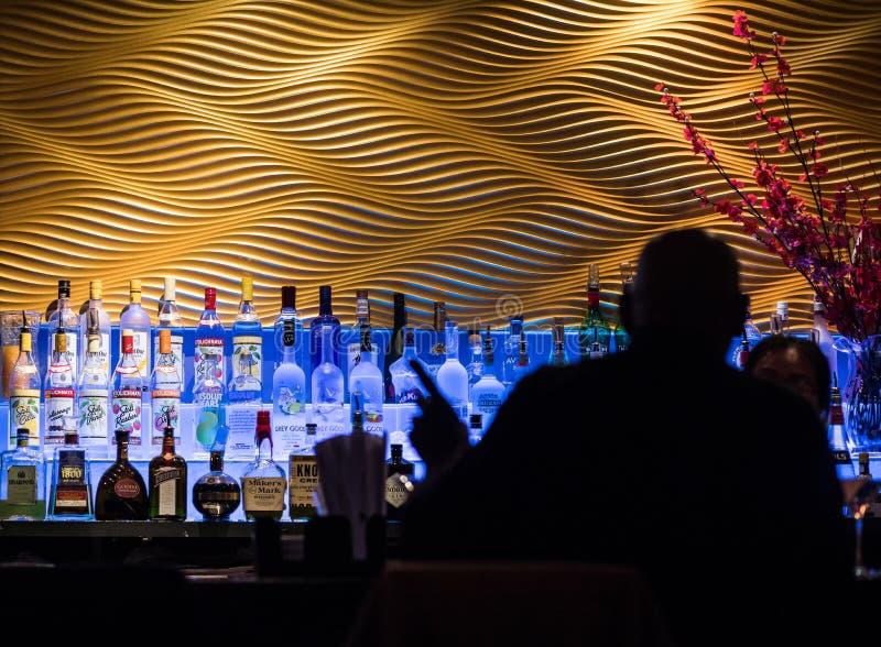 Человек в силуэте на баре приказывая питье в сушах Restaur стоковое фото rf