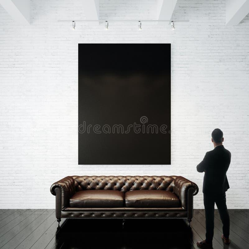 Человек в современном костюме смотря черный пустой холст держа дальше белую кирпичную стену вертикально стоковые изображения