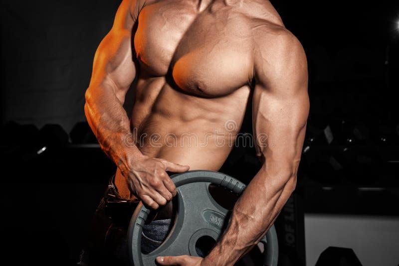 Человек в спортзале Мышечный парень культуриста делая тренировки с штангой Сильная персона с напряженной мужской рукой с штангой  стоковые изображения rf