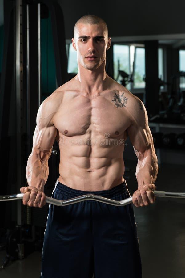 Человек в спортзале работая бицепс с штангой стоковое изображение rf