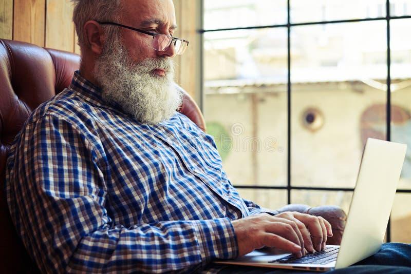 Человек в стеклах сидя на кресле и работая с компьтер-книжкой стоковая фотография rf