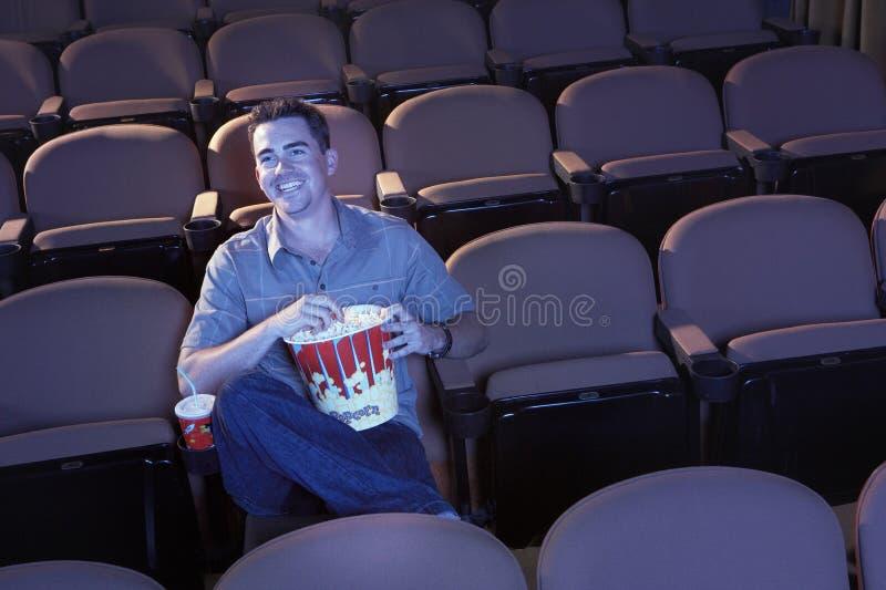 Человек в театре смотря кино стоковое изображение rf