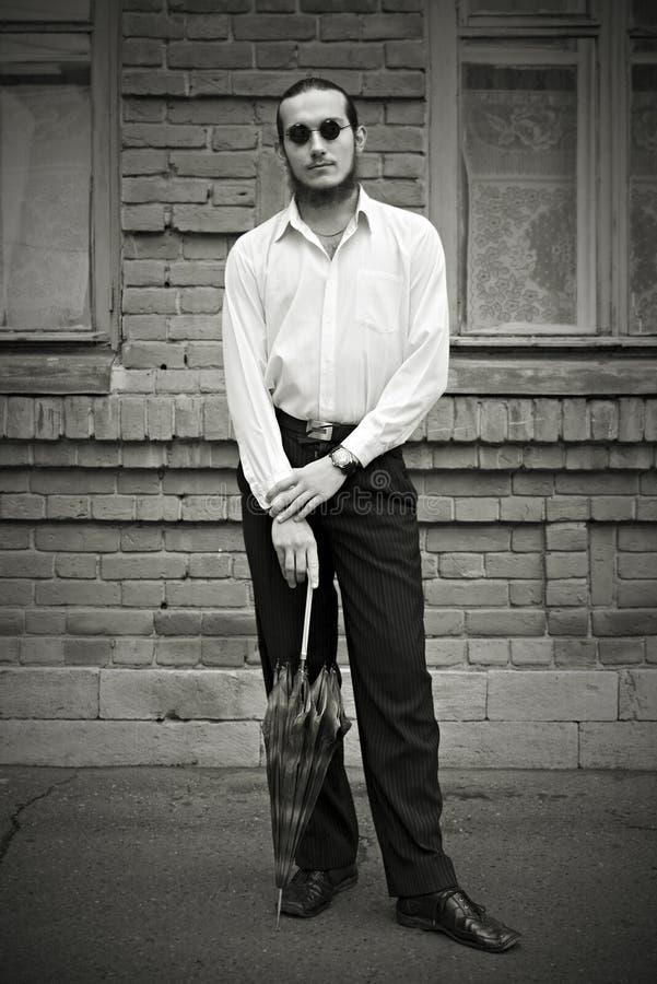 Человек в темных стеклах с зонтиком на улице города стоковая фотография rf