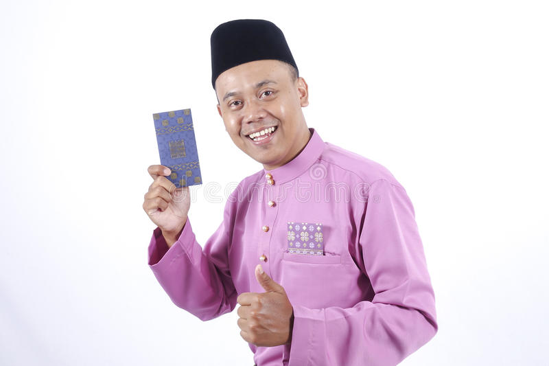 Человек в традиционной одежде жизнерадостной с пакетом денег во время празднует Eid Fitr стоковая фотография rf