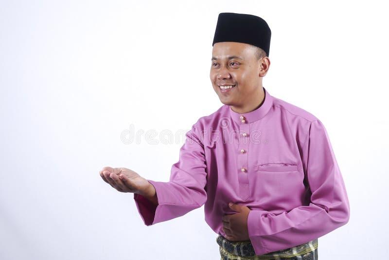 Человек в традиционной одежде, стоя празднует Eid Fitr стоковое изображение