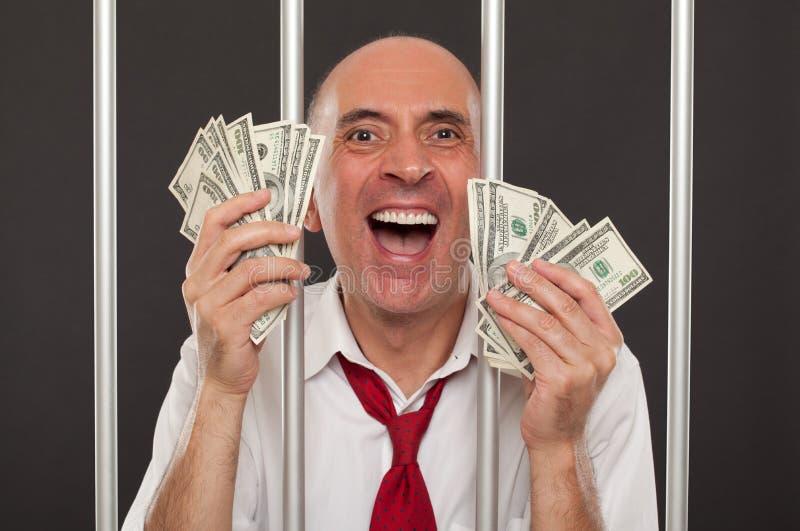 Человек в тюрьме смеясь над с наличными деньгами стоковые фотографии rf