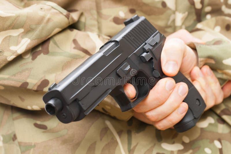 Человек в черной маске держа оружие за его назад стоковые фото
