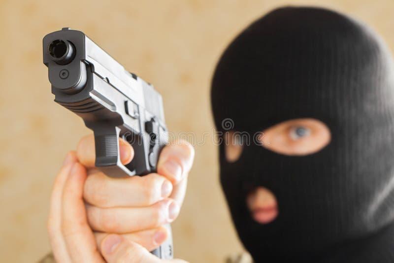 Человек в черной маске держа оружие и подготавливает для того чтобы использовать его стоковые фотографии rf