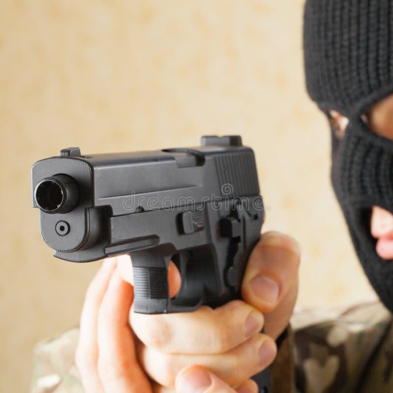 Человек в черной маске держа оружие перед им - съемка студии стоковое изображение