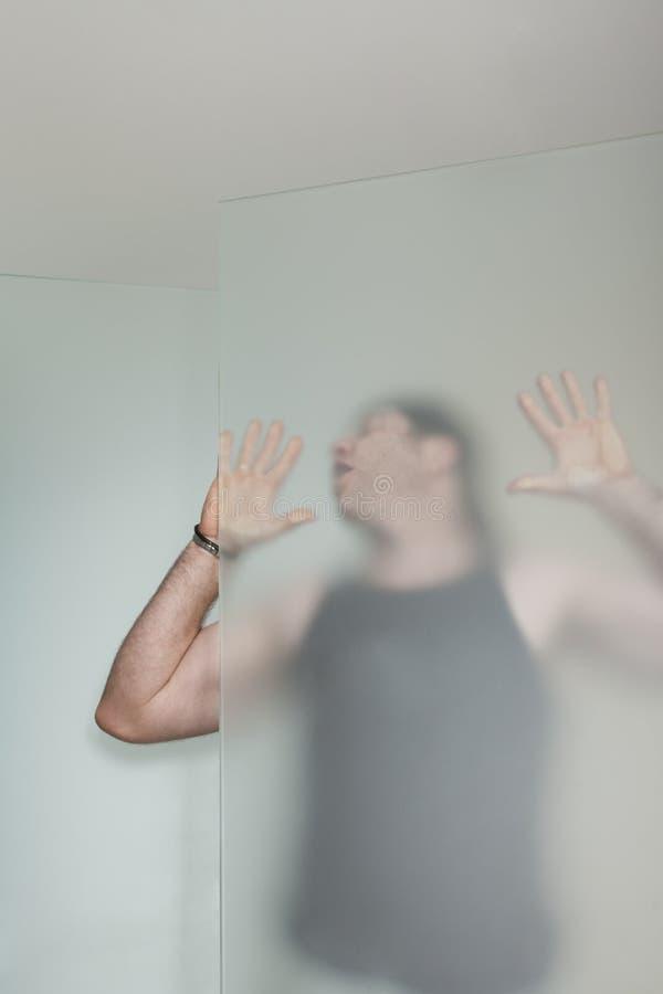 Человек в черном танке за стеклянной дверью стоковое изображение