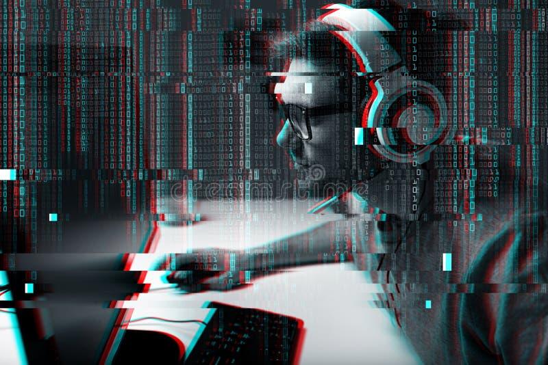 Человек в шлемофоне играя видеоигру компьютера дома стоковые изображения