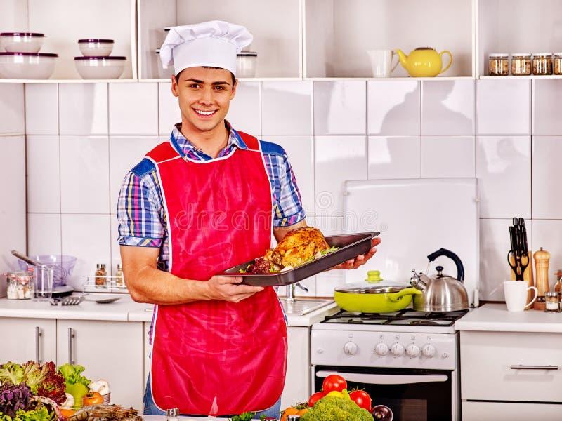 Человек в шляпе шеф-повара варя цыпленка стоковые фото