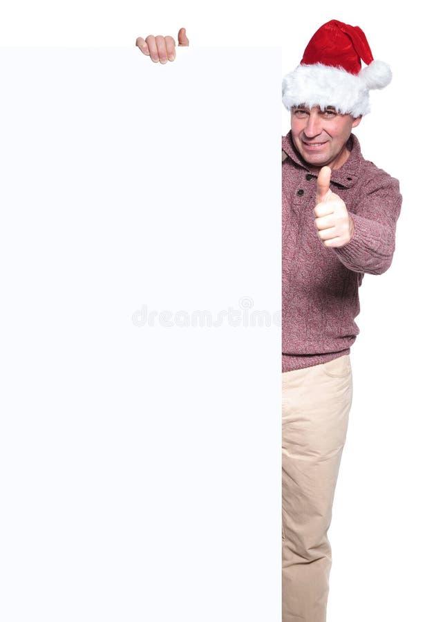 Человек в шляпе santa с большой пустой доской и делать одобренный знак стоковые изображения rf