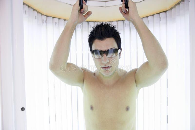 Человек в sunbath получая высокую степень  стоковое фото
