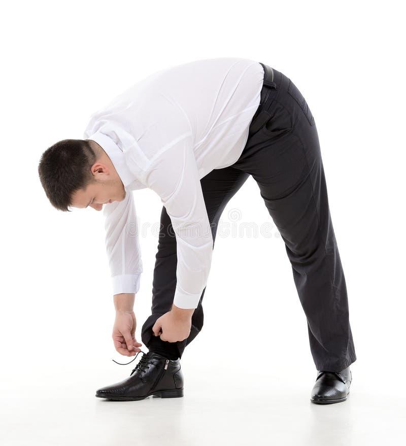 Человек гнуть вниз для того чтобы сделать вверх по его шнуркам стоковое изображение rf
