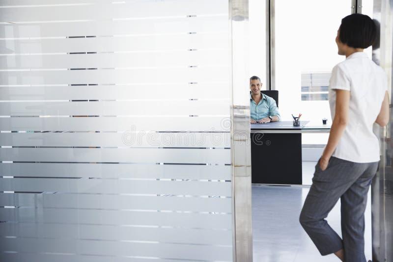 Человек говоря к женщине стоя в входе офиса стоковая фотография