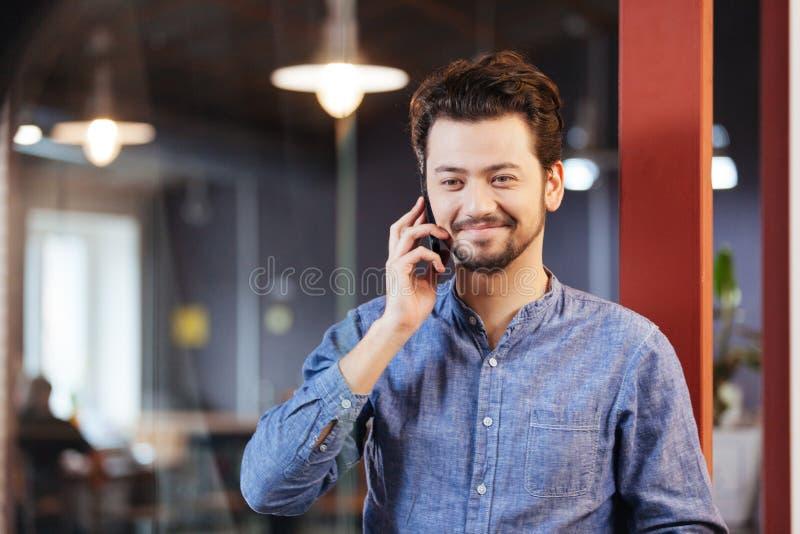 Человек говоря на телефоне в офисе стоковое изображение