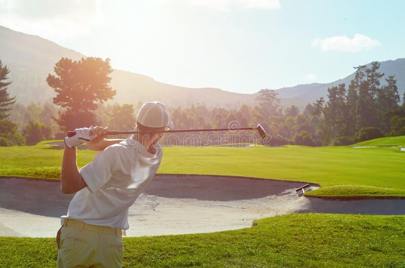 Человек гольфа принимает качание над бункером стоковые изображения rf