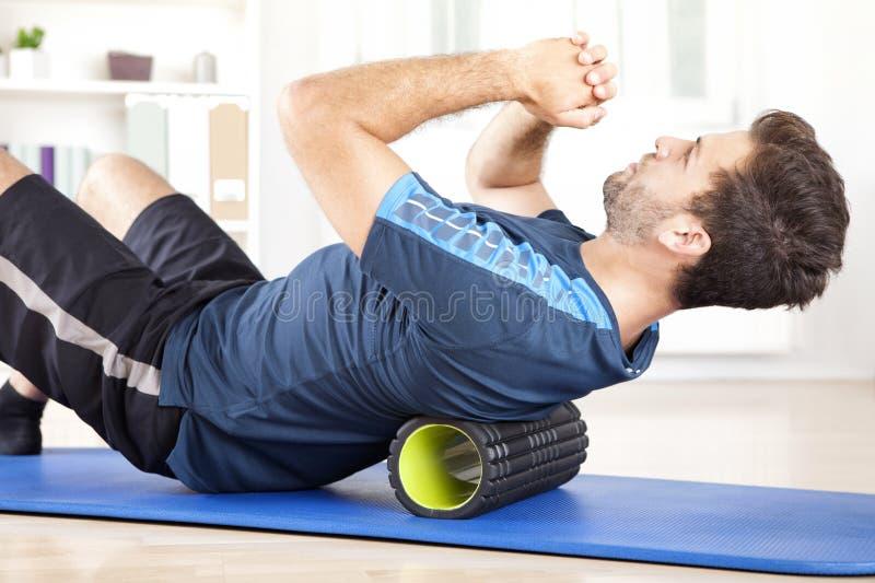Человек лежа на ролике пены пока делающ тренировку стоковые фотографии rf