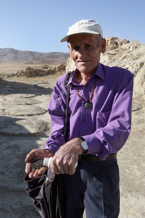 Человек держа зерно на бывших королях дворце Urartu Sarduri-Hinili размещал около Cavustepe в дальневосточной Турции стоковые фотографии rf