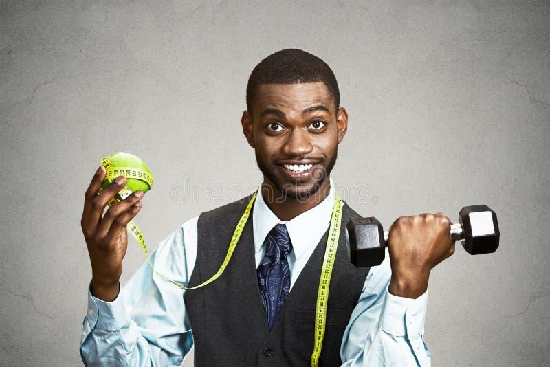 Человек держа зеленую гантель яблока стоковые изображения