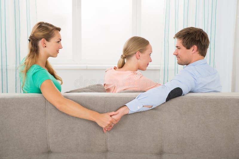 Человек держа руки другой женщины пока смотрящ подругу стоковая фотография