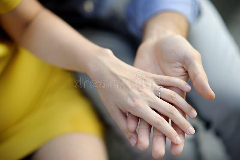 Человек держа руку женщины с обручальным кольцом стоковая фотография