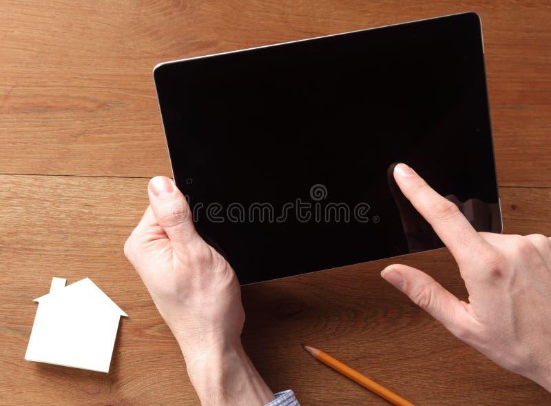 Человек держа таблетку пока касающся экрану стоковые изображения