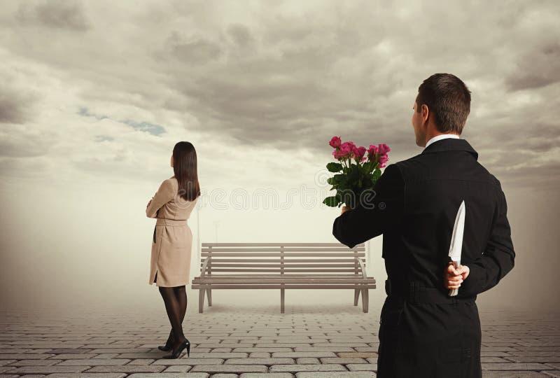 Человек держа цветки и заднюю часть ножа позади стоковая фотография