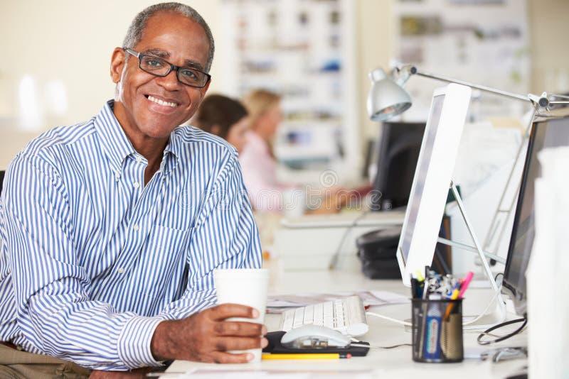 Человек держа чашку работая на столе в многодельном творческом офисе стоковая фотография